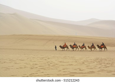 DUNHUANG, GANSU, CHINA- MARCH 11, 2016: Group of tourists are riding camels in the desert at Mingsha Mountain in Dunhuang, China. This is a famous place part of silk road in Dunhuang.