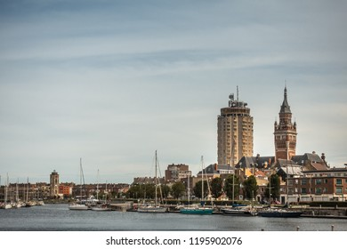 Dunkerque, France - September 16, 2018: Old Port with sailing yachts and three towers, LTR: Leughenaer historic lightower, condominiums, Belfry of Dunkirk town hall under light blue skay.