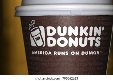 Dunkin Donuts brown coffee cup macro close up America runs on dunkin slogan January 13, 2018. Saint Augustine, Florida / USA