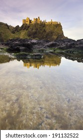 Dunluce Castle in early morning light, reflected in a seaside puddle.