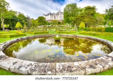 Dunrobin Castle reflected on the pond inside a beautiful and spectacular park that surrounds it. Dunrobin gardens have beautiful fountains, and labyrinth hedges. Scottish Highlands, Scotland, UK.