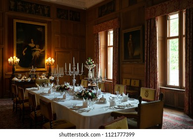 Dunrobin castle, Scotland - June 08, 2018: Set table in the large dining room, richly decorated with pictures