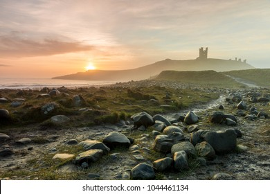 Dunstanburgh Castle / England, March 11 2018 - Northumberland coastal walk following the recent storm. Rocks moved onto the path, mist and fog rising from the sea at sunrise.