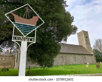 DUNWICH, SUFFOLK - APRIL 24, 2018: Village sign beside St James Church the in the village of Dunwich, Suffolk, UK.