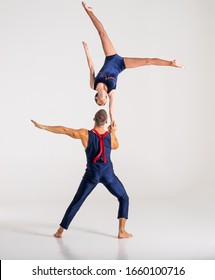 Duo Of Acrobats Showing hand to hand Trick, Isolated On White