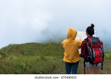 Duo female hiker with backpack reading and searching map while way of mountain was covered by heavy mist.