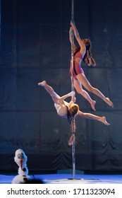 The duo of a girl athlete gymnasts show a pair acrobatic performance on the pylon.