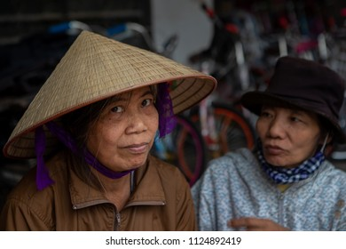 Duong Lam, Ha Noi, Vietnam-April 18, 2018: Vietnamese woman vendor in the street market of the ancient city Duong lam looks at the camera.