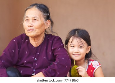 DUONG LAM, VIETNAM- SEPT 3: An unidentified Vietnamese child sits with her grandmother on September 3, 2010 in Duong Lam Village, Vietnam. The median age of population in Vietnam is 27.8 years old.