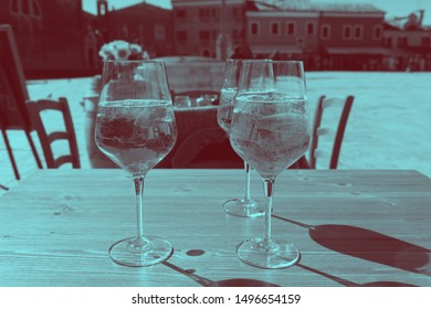 Duotone image, dark and cyan blue. three glasses of fresh drinks with architecture reflections. Venice Italy.
