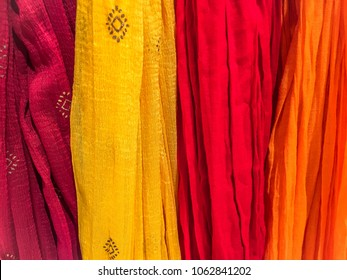 Dupattas of different colors hanging on a wall at an indian shop. Can be used as background or texture. Dupatta is a colorful shawl like scarf worn by Indian women, usually matched with the garments