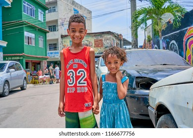 Duque de Caxias, Rio de Janeiro, Brazil -  December 10, 2018: Young Brethren of Brazilian Favela Holding Hands Candid Portrait in Slum Suburb Colored SunLight tone