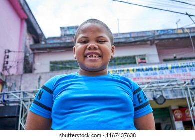 Duque de Caxias, Rio de Janeiro, Brazil -  December 10, 2018: Brazilian Black Young Boy Toothless Smile Candid Face Inside Favela Subculture Childhood an Youth Lifestyle