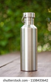 Durable, high quality reusable stainless steel bottle as alternative to plastic bottles. Toxin, BPA, plastic free zero waste option for drinking tap water at home or at the office. Dark wooden surface