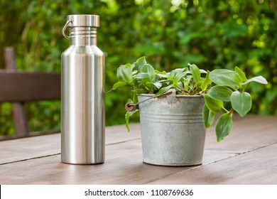 Durable, high quality reusable stainless steel bottle as alternative to plastic. Toxin, BPA, plastic free zero waste option for drinking tap water at home or the office. Next to a potted plant on wood