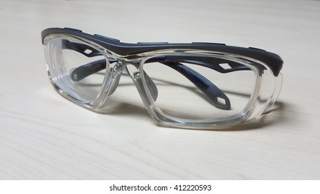 Durable safety glasses for Oil & Gas industry workers isolated on white wooden background.