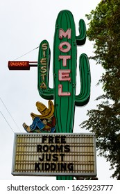 """Durango, Colorado - May 30 2019: Close up of the sign of the Siesta Motel, opened 1956. Under the neon sign reads """"Free rooms, just kidding."""" Vertical shot."""
