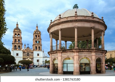 """Durango, Mexico, April 2019. Catedral de Durango (Durango Cathedral)  and """"Plaza de Armas"""". The names of the city founders are written with copper letters at the top of the kiosk."""