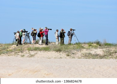 Durankulak, Bulgaria - April 30, 2019:  Small group of retired people birdwatchers with binoculars and photo cameras with telescopic lenses high on the dunes by Durankulak Lake in Durankulak nature re