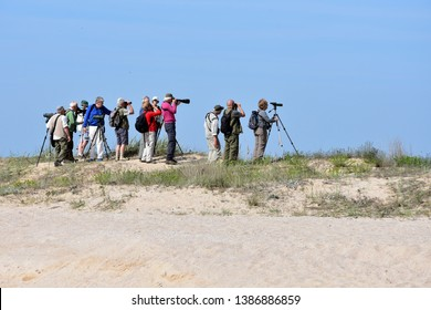 Durankulak, Bulgaria - April 30, 2019: Small group of retired people birdwatchers with binoculars and photo cameras with telescopic lenses standing on the dunes by Durankulak Lake in Durankulak nature