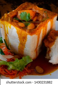 A Durban Bunny Chow - or, in this case, a vegerarian quarter bean bunny - served with sambals. This is an iconic Durban meal consisting of a section of a hollowed out loaf of bread filled with beans.