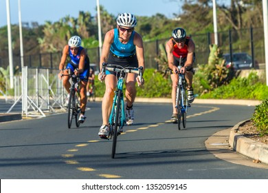 Durban, KZ-Natal / South-Africa - March 24,2019: Triathlon national champs cycling action men and women on road course along beachfront, closeup photo of athletes.