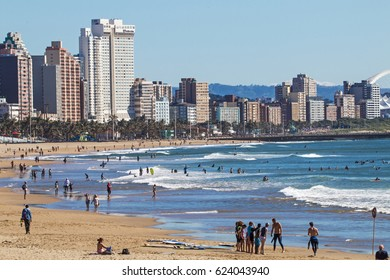 DURBAN, SOUTH AFRICA - APRIL 15 , 2017: Many unknown people on early morning beach against beachfront and city skyline in Durban, South Africa