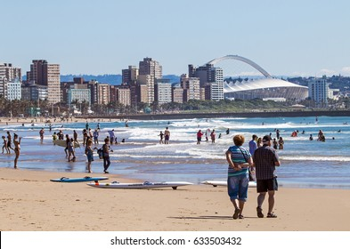 DURBAN, SOUTH AFRICA ; APRIL 24, 2017: Many unknown people on morning visit to beach against Durban city skyline and Moses Mabhida Stadium  in South Africa
