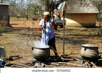 DURBAN, SOUTH AFRICA - August 1: Zulu women cooking in a traditional pot, outdoors in a rural homestead of Kwa Zulu Natal, South Africa on August 1, 2015