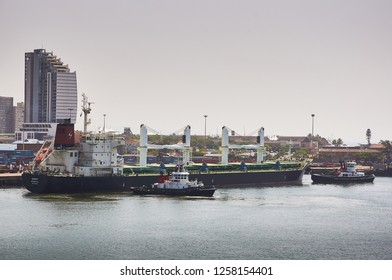 Durban, South Africa - Circa February 2018: Large bulk carrier ship unmooring in Durban port with two tug boats in Durban port.