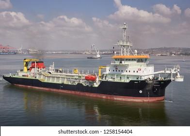 Durban, South Africa - Circa February 2018: Dredger ship performing dredging operations inside Durban port.