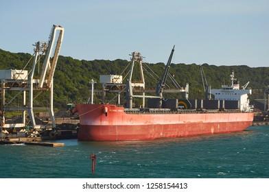 Durban, South Africa - Circa February 2018: Large bulk carrier alongside a pier in Durban port loading cargo.