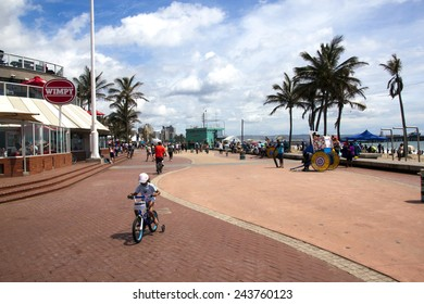 DURBAN, SOUTH AFRICA - DECEMBER 28, 2014: Many unknown adult and children cyclists and pedestrians on promenade on beach front in Durban, South Africa