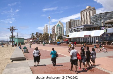 """DURBAN, SOUTH AFRICA - DECEMBER 28, 2014:  Many unknown people walk and cycle along promenade on """"Golden Mile"""" beach front in Durban, South Africa"""