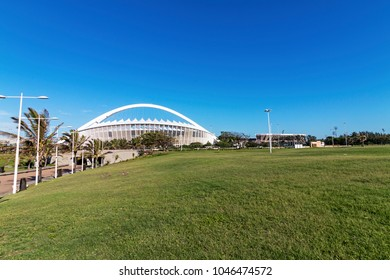 DURBAN, SOUTH AFRICA - FEBRUARY 2018: Early morning empty grass lwn recreational area against Moses Mabhida Stadium and blue sky in Durban, South Africa