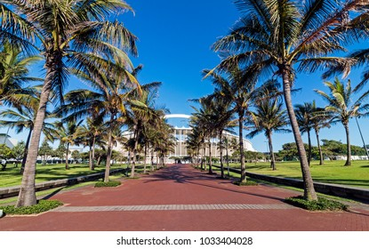 DURBAN, SOUTH AFRICA - FEBRUARY 23, 2018: Morning empty palm tree lined paved walkway leading towards Moses Mabhida stadium and clear blue sky in Durban, South Africa