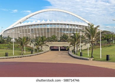 DURBAN, SOUTH AFRICA - FEBRUARY 24, 2017: Early morning, paved promenade, green grass lawn and palm trees against Moses Mabhida Stadium and  blue cloudy sky background in Durban, South Africa