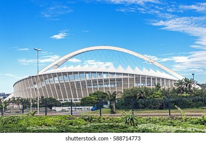 DURBAN, SOUTH AFRICA - FEBRUARY 24, 2017: Early morning, green vegetation against Moses Mabhida Stadium and  blue cloudy sky background in Durban, South Africa