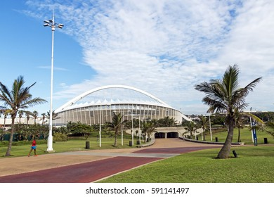 DURBAN, SOUTH AFRICA - FEBRUARY 24, 2017:  Unknown early morning jogger,  promenade, green grass lawn and palm trees against Moses Mabhida Stadium and  blue cloudy sky  in Durban, South Africa
