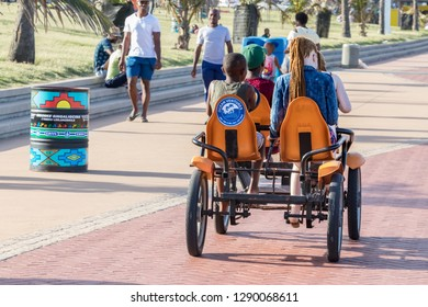 Durban, South Africa - January 06th, 2019: Two black boys and two white-caucasian girls sharing a quadricycle for a ride in the beach of Durban, South africa.