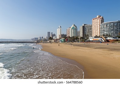 DURBAN, SOUTH AFRICA - JANUARY 24, 2017 : Few unknown people on early morning beachfront against city skyline and blue sky in Durban, South Africa