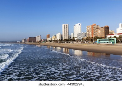DURBAN, SOUTH AFRICA - JUNE 24, 2016: Early morning  empty beach ocean and palm trees against Golden Mile city skyline in Durban, South Africa