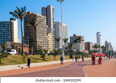 DURBAN, SOUTH AFRICA - JUNE 6, 2015 : Morning view of many unknown people on paved promenade against city skyline on Durban beachfront in South Africa