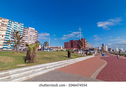 DURBAN, SOUTH AFRICA - MARCH 12 , 2018: Many early morning visitors walk along paved quiet beachfront promenade against blue cloudy city Durban beachfront cityscape in South Africa