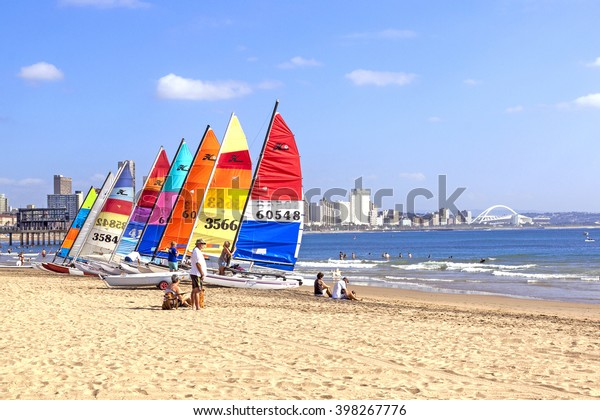 DURBAN, SOUTH AFRICA ; MARCH 28, 2016:Many unknown people and colorful sail boats on Vetch's beach in Durban South Africa