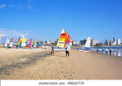DURBAN, SOUTH AFRICA ; MARCH 28,2016: Many unknown people and colorful sailing boats stacked on Vetch's beach and city skyline in Durban South Africa