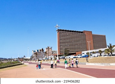 """DURBAN, SOUTH AFRICA - SEPTEMBER 21, 2014: Many unknown people walk along promenade in front of residential complexes on """"Golden Mile Beachfront"""" in Durban, South Africa"""