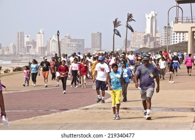 DURBAN, SOUTH AFRICA - SEPTEMBER 24, 2014:Many unknown  National Heritage Day walk participants walk along beachfront promenade in Durban, South Africa