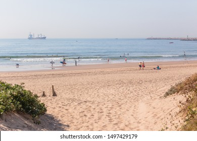 Durban south beach holiday public surfing swimming scenic landscape ocean small waves warm climate with ship entry towards harbor port piers.