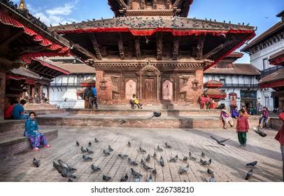 DURBAR SQUARE, KATHMANDU, NEPAL - APRIL 4, 2014: Nepali people sitting at old pagodas near museum of Tribhuvan Nepali King